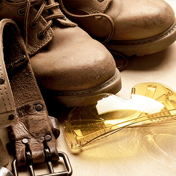 Ausschnitte von Arbeitsstiefeln und eine gelbe Schutzbrille