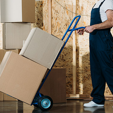 Transportkarre mit Paketen, die von Lieferanten geschoben wird