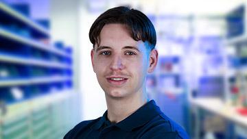 ein Portrait von einem Mitarbeiter in einem blauen Shirt