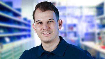 ein Portrait von einem Mitarbeiter mit blauem Shirt