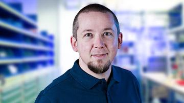 ein Portrait von einem Mitarbeiter mit blauem Oberteil
