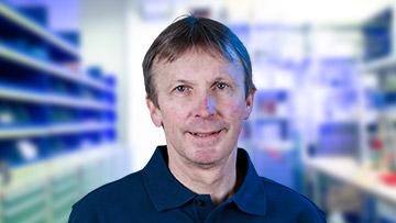 Portrait von einem Mitarbeiter mit blauem Shirt