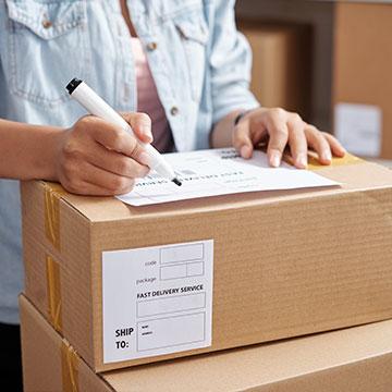 Person, die die Adresse auf ein Paket schreibt