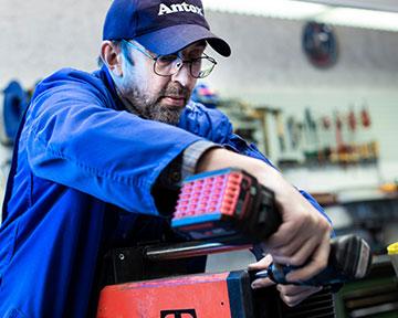 Mitarbeiter in blauer Kappe, der mit einer Akku-Maschine ein roten Gerät repariert