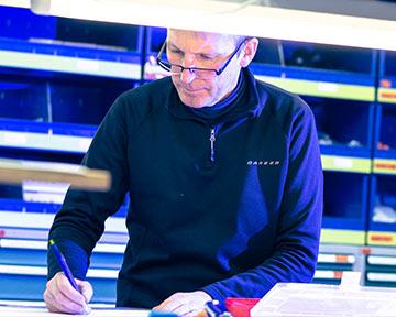 Ein Mann mit Brille, der an einem Tisch steht und etwas aufschreibt
