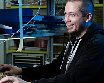 Mitarbeiter in schwarzem Kapuzen-Pulli am Computer