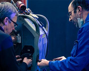 zwei Männer, die zusammen an einer Industrie-Maschine mit Werkzeug arbeiten