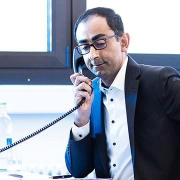 Ein Foto vom Geschäftsführer beim Telefonieren am Schreibtisch